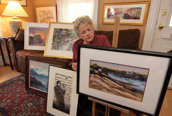 Allegra Boverman/Gloucester Daily Times. Ruth Brown of Rockport talks about the works of art she has been collecting over the years including the works near her. From left on the couch are a work by Ruth Minas, a work by Betty Lou Schlemm; at her feet from left are works by Mary McGlyn, Peter Bodge and on the easel, Frank Federico. On the wall behind are, from left: a work by Florence Bradenberg and Tom Sutherland.
