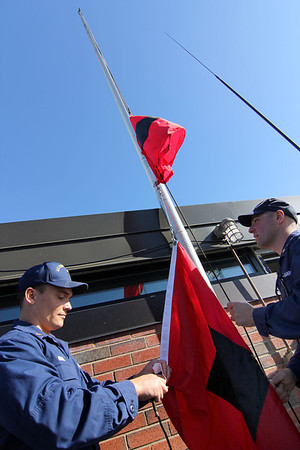 ALLEGRA BOVERMAN/Gloucester Daily Times These are the hurricane warning flags that the U.S. Coast Guard puts up on their rooftop flagpole to alert mariners that winds are 74 miles per hour or higher. From left are <br /> are Sean Gross of Seattle and Petty Officer Tom Moen of Foxborough.