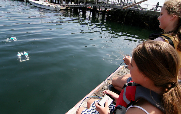 ALLEGRA BOVERMAN/Staff photo. Gloucester Daily Times. Gloucester: <br /> Carli Heckman and Emily Kenyon, both O'Maley Middle School students, test their remote-operated vehicles, or ROVs, which are submersible, that they built at Maritime Gloucester on Thursday afternoon. They  are among 40 students are taking part in the two-week long Summer Engineering Adventure, which is a partnership of Maritime Gloucester, MIT's Edgerton Center, and O'Maley Middle School and the Gloucester Education Foundation. The students rotate between projects in Gloucester at Maritime Gloucester and on the Cambridge campus.