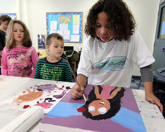 """Allegra Boverman/Gloucester Daily Times. Ilyana Lorenzana, 8, right, works on her painting while from left: Aubrey Bertolino, and Jude Ventura, both 6, watch during the Art Club session at Pathways for Children on Thursday. The participating kids' paintings will be auctioned at the upcoming """"A Place at the Table"""" gala on Nov. 9."""