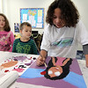 "Allegra Boverman/Gloucester Daily Times. Ilyana Lorenzana, 8, right, works on her painting while from left: Aubrey Bertolino, and Jude Ventura, both 6, watch during the Art Club session at Pathways for Children on Thursday. The participating kids' paintings will be auctioned at the upcoming ""A Place at the Table"" gala on Nov. 9."