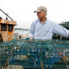 Allegra Boverman/Gloucester Daily Times. Salvatore Parisi of Gloucester, left, captain of the lobster boat Iliana John, and boat owner Jon Cowles of Maine, prepare, tune up and repair about 50 lobster traps before setting them out on Thursday.