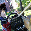 Allegra Boverman/Gloucester Daily Times.  Julian Morais, 5, of Danvers, left, turns the wheel of an old-fashioned cider press being manned by Cogswell's Grant volunteer Jonathan Guerin on Saturday during Pumpkin Day activities at the historic farm in Essex. Julian's brother Marcus Morais, 3, was looking on, center back.