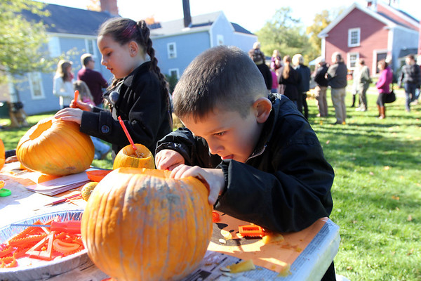 Allegra Boverman/Gloucester Daily Times. Anthony Madden, 5, and his sister Aliyah Madden, 7, both of Charlestown and visiting their grandmother in Gloucester, were intently carving their pumpkins during Pumpkin Day activities at Cogswell's Grant in Essex on Saturday. Anthony's was going to have a monster face, Aliyah's was to have a vampire's face, they said.