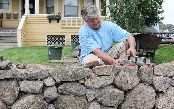 """Allegra Boverman/Gloucester Daily Times. Steve Pierce has been working to repair a stone wall at one of his properties he owns in Gloucester along Washington Street. The wall was damaged when a car hit it some time ago. He works on it with Dusty Rhodes of Gloucester when they can. Pierce used to do auto body work, so rebuilding stone walls is a new endeavor for him. """"It's not going to be pretty,"""" he said of the work he's doing on the wall, """"but it's going to be functional."""""""