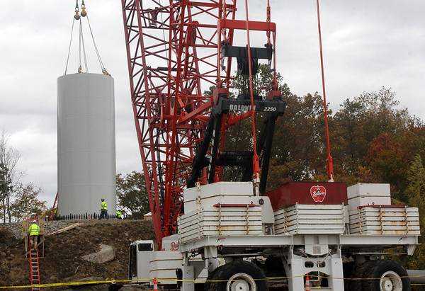Allegra Boverman/Gloucester Daily Times. The base of the wind turbine was being installed on Friday at Varian division of Applied Materials in Blackburn Industrial Park.
