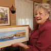 Allegra Boverman/Gloucester Daily Times. Ruth Brown of Rockport talks about the works of art she has been collecting over the years, including the piece in her hands by Ann Fisk and Carole Moore, on the wall at upper left.