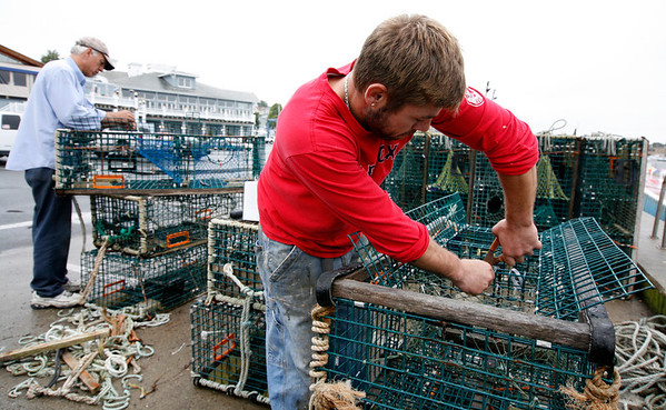 Allegra Boverman/Gloucester Daily Times. Salvatore Parisi of Gloucester, right, captain of the lobster boat Iliana John, and boat owner Jon Cowles of Maine, prepare, tune up and repair about 50 lobster traps before setting them out on Thursday.