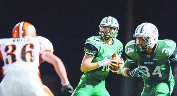 PAUL BILODEAU/Staff photo<br /> <br /> Manchester-Essex's quarterback Graig Carter is forced out of the pocket during the Hornets' game against Ipswich at Hyland Field in Manchester last night.