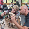 DESI SMITH/Staff photo. Brendan Johnson, (left) a student teck at O'maley, who has experience in building a 3_D printer, helps out volunteer Haig Demarjian with the belt during a mass build at the O'Maley School Saturday morning. Groups of volunteers, up tp 50 in all, organizied to assemble  24 new 3_D printers for O'Maley studetns in the O'Maley 3D Print Lab.  All 24 printers were purchased by Gloucester Education Foundation.  Oct 4,2014