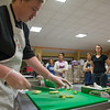 Desi Smith Photo.   Dan McKenna (left) a cook from Short and Main, shows how to slice fennel that will be used in the making of mirepoix,Tuesday night at the Open Door on Emerson Ave, were quest learn to cook using local harvest.   October 18,2016