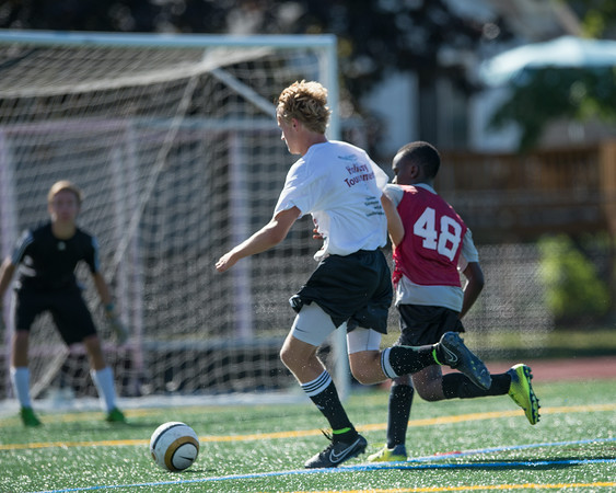 DESI SMITH/Staff photo.  Manchesters George Lantz (left) takes the ball to the goal, as Gloucesters _____________try's to defend,in a Soccer Jamboree held saturday morning at New Balance Track and Field at Newell Stadium.   August 30,2014
