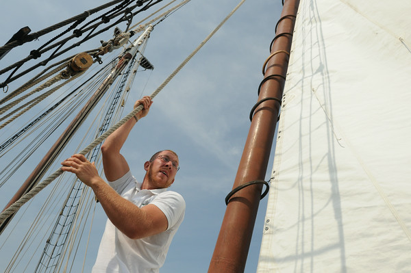 PAUL BILODEAU/Staff photo. Derek Hoffmann, a crew member on on the Liberty Clipper, which is based out of Boston, helps pull up one of the sails during the 30th annual Gloucester Schooner Festival.