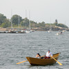 PAUL BILODEAU/Staff photo. A rower in a dory passes Ten Pound Island during on the Liberty Clipper, which is based out of Boston, during the 30th annual Gloucester Schooner Festival.