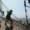 PAUL BILODEAU/Staff photo. A crew member on the Liberty Clipper, which is based out of Boston, pulls up the outer jib during the 30th annual Gloucester Schooner Festival.