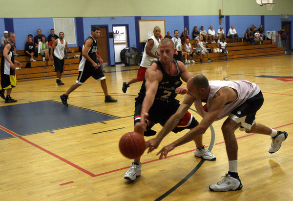 Gloucester: Flynn's Physical Therapy's Dave Stantial, left, knocks the ball from Crow's Nest's Zach Zegaroski during the Cape Ann YMCA Summer League Championship last night. Photo by Kate Glass/Gloucester Daily Times Tuesday, September 1, 2009