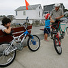"Rockport: Sean Whelan stares down at the brand new bike that he got for his 9th birthday, which is Saturday, as his father, Bob Whelan, helps his sister, Shannon, 5, with her bike helmet while riding along Front Beach yesterday afternoon. The pedals on Sean's bike broke and the rest of the family rode home to get the car so they could bring the bike back to the store. Sean said the bike was ""great while it worked."" Photo by Kate Glass/Gloucester Daily Times Tuesday, September 22, 2009"