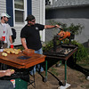 Gloucester: Pat Riley peals potatoes and Matt Bouffard baste a pig over some charcoles as Arron Pinegar (white cap) and Jon Keyes look on.Its their end of the season cookout Sunday on Centenial Ave.Desi Smith Photo/Gloucester Daily Times. September 20,2009.