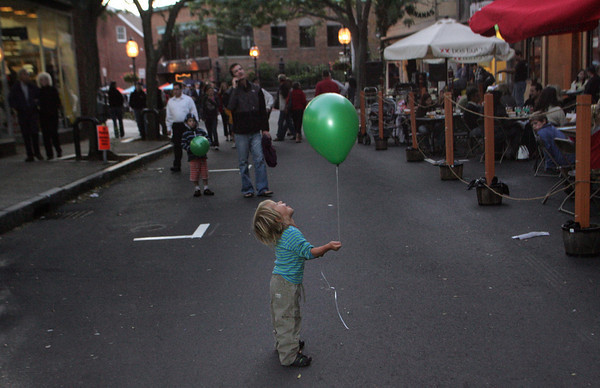 Gloucester: Nikko Thomas, 2, of Gloucester looks up to see a friend who was calling his name from a balcony over looking Mains Street as Nikko was enjoying the Block Party with his family Saturday evening. Mary Muckenhoupt/Gloucester Daily Times
