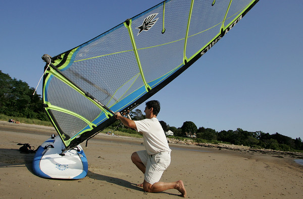 """Gloucester: Tim Moutafis of Lanesville gets ready to go windsurfing on Niles Beach Wednesday afternoon. Moutafis has been battling Parkinson's Disease for 20 years and believes wind surfing helps him fight the disease. """"Wind Surfing makes your body go beyond it's limits"""" Moutafis says explaining that people with Parkinson's Disease tend to live within the limits that the disease regulates. Because a windsurfer must push beyond his or her limits while out of the water wind surfing is a great exercise for someone like Moutafis, who is refusing to let a debilitating condition stop him from living life to the fullest.  Moutafis windsurfs all year long and tries to go out twice a week. Mary Muckenhoupt/Gloucester Daily Times"""