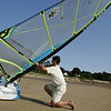 "Gloucester: Tim Moutafis of Lanesville gets ready to go windsurfing on Niles Beach Wednesday afternoon. Moutafis has been battling Parkinson's Disease for 20 years and believes wind surfing helps him fight the disease. ""Wind Surfing makes your body go beyond it's limits"" Moutafis says explaining that people with Parkinson's Disease tend to live within the limits that the disease regulates. Because a windsurfer must push beyond his or her limits while out of the water wind surfing is a great exercise for someone like Moutafis, who is refusing to let a debilitating condition stop him from living life to the fullest.  Moutafis windsurfs all year long and tries to go out twice a week. Mary Muckenhoupt/Gloucester Daily Times"