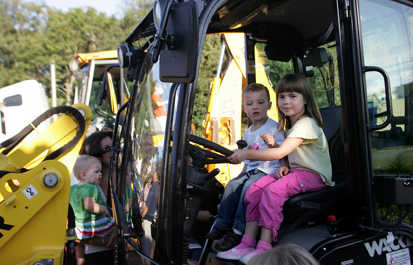 Essex: Emily Doucette, 5, and Cullen MacWhinnie, 2, sit in a front loader while checking on the construction equipment during the Touch a Truck program offered by the TOHP Burnham Library behind the Essex Police and Fire Stations Thursday evening. Mary Muckenhoupt/Gloucester Daily Times