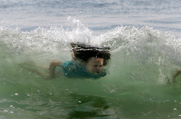 Rockport: Zoe Narkewicz, 10, swims through a wave while playing in the water with her friend Sophie Bannerman, 9, at Cape Hedge Beach Saturday afternoon.  Mary Muckenhoupt/Gloucester Daily Times