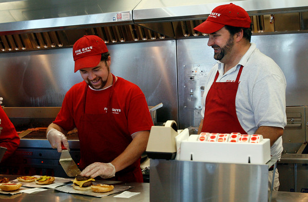 Gloucester: Chris Collins, left, and Steve Margiotta, right, assemble burgers at Five Guys Burgers and Fries, which opened at Gloucester Crossing yesterday. Photo by Kate Glass/Gloucester Daily Times Monday, September 21, 2009