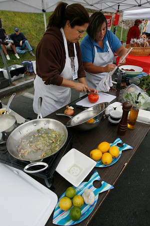 Gloucester: Lisa Van Sand and Jessica O'Leary cut up vegetables for their dishes during the Seafood Throwdown at the Cape Ann Farmers Market. Chefs  Photo by Kate Glass/Gloucester Daily Times Thursday, September 17, 2009