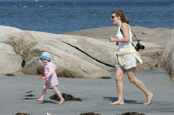Gloucester: Chassea Robinson of Magnolia chases after her daughter Blakeley, 2, while enjoying the warm weather at Wingearsheek Bech Friday afternoon. Mary Muckenhoupt/Gloucester Daily Times