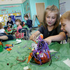 Gloucester: Ewan McCarthy checks out the crazy pumpkin creation his classmate Sarah-Jean Collins made as the students decorate pumpkins in Jaclyn Figurido's class at West Parish Elementary School Friday morning.  The kindergarten class decorated pumpkins to be entered into a pumpkin decorating contest at the Topsfield Fair. Also pictured is Mathieu Fuller, left. Mary Muckenhoupt/Gloucester Daily Times