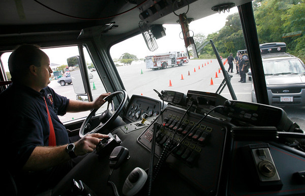 Gloucester: Gloucester Firefighter Darryl Wonson takes his turn at the wheel during Emergency Vehicle Operational Strategies training at Stage Fort Park yesterday afternoon. The training, which is paid for through the city's insurance company, includes 4 hours of classroom training with instructor Ken Jones and 4 hours of practice maneuvering the vehicles through an obstacle course in an effort to reduce accidents and increase efficiency. Every firefighter and paramedic will complete the training by the end of the week and the city will receive a discount on their insurance as a result. Wonson, who has 14 years experience driving the fire engine, had no trouble with the course, though others felt the cones were a little too narrow. Photo by Kate Glass/Gloucester Daily Times Thursday, September 24, 2009
