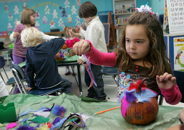 Gloucester: Christina Polsonetti puts the final touches on her pumpkin in Jaclyn Figurido's class at West Parish Elementary School Friday morning.  The kindergarten class decorated pumpkins to be entered into a pumpkin decorating contest at the Topsfield Fair. Mary Muckenhoupt/Gloucester Daily Times