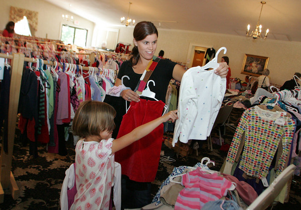 Essex: Karin Montoya gets a second opinion on a shirt form her daughter Sofia, 5, while purusing through some clothes for her daughters at the Children's Drop and Shop at Woodman's Function Hall Friday afternoon. The Children's Drop and Shop, a consignment event offering gently used clothing, toys, carriages and more, will be open today from 10 a.m. to 5 p.m. and Sunday noon to 5 p.m. with all items sold at 50% off on Sunday. Mary Muckenhoupt/Gloucester Daily Times