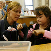 Essex: Wynn Gerhardt watches as her daughter, Bonnie Gerhardt, cuts out a tracing of her hand to make bat wings at the TOHP Burnham Library yesterday afternoon. Bonnie was having trouble with the left-handed scissors because they were not sharp enough. Photo by Kate Glass/Gloucester Daily Times Wednesday, September 30, 2009