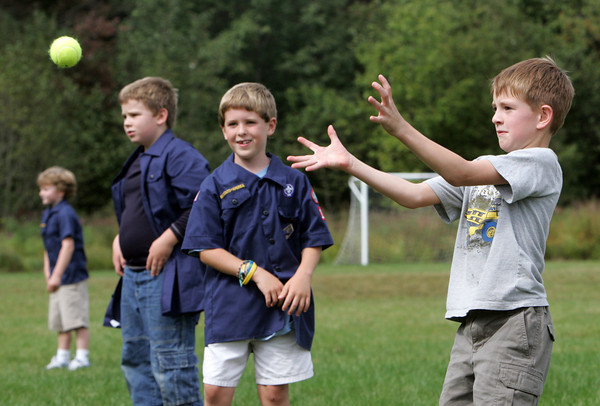 Essex: Travis Duncan, 7, waits to catch a tennis ball while playing a game as the Wolf Cubs of Pack 100 Cub Scout Troop have their first meeting behind Essex Elementary School Wednesday afternoon.  Also pictured is Issac Notte, 7, center, and Luke Dawson and Ethan Wilbur, right. Mary Muckenhoupt/Gloucester Daily Times
