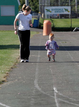 Gloucester: Kara Holmquist of Boston goes around the track at the O'Maley School with her daughter, Story Bracker, 14 months, as they prepare for the Children's Fun Run as part of the 76th Around Cape Ann Race, which benefits the Cape Ann YMCA. Photo by Kate Glass/Gloucester Daily Times Monday, September 7, 2009