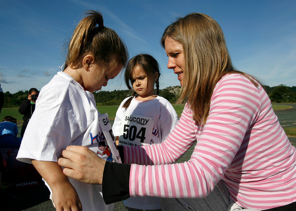 Gloucester: Lindsay Carroll of Gloucester helps her daugters, Cameron, 3, and Maddison, 4, put their numbers on before competing in the Children's Fun Run at the O'Maley School yesterday morning. The race was part of the 76th Around Cape Ann Race, which benefits the Cape Ann YMCA. Photo by Kate Glass/Gloucester Daily Times Monday, September 7, 2009