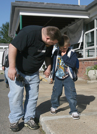 "Gloucester: Grant Harris comforts his son, Gavin Harris, 6, as they arrive at West Parish Elementary School for the first day of school yesterday morning. After Gavin found his first grade teacher, he started smiling, and said the tears he cried earlier were ""tears of joy."" Photo by Kate Glass/Gloucester Daily Times Tuesday, September 1, 2009"