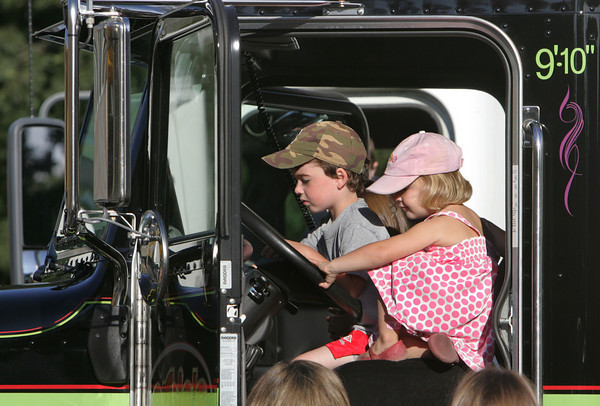 Essex: Brady Friedrich, 5, and Willa Paglierani, 3, check out what it's like to be in the driver's seat of a tow truck during the Touch a Truck program offered by the TOHP Burnham Library behind the Essex Police and Fire Stations Thursday evening. Mary Muckenhoupt/Gloucester Daily Times
