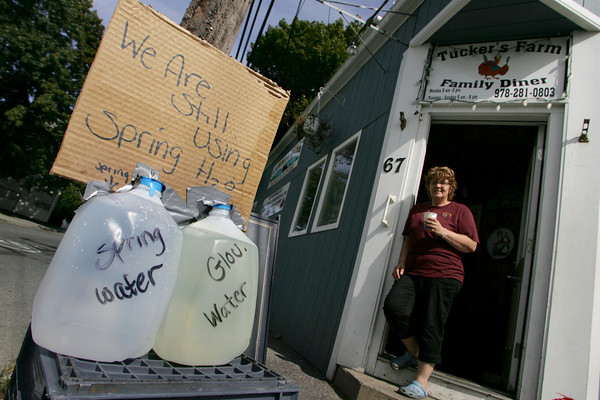 Gloucester: Eleanor Tucker has two bottles of water in front of her restaurant Tucker's Farm Family Diner showing how murky Gloucester water is as opposed to spring water.  Tucker says that she will continue to serve spring water to her customers until Gloucester water runs clear. Gloucester lifted the boil water order Wednesday. Mary Muckenhoupt/Gloucester Daily Times