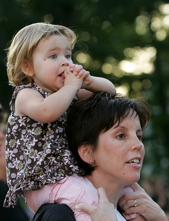 Gloucester: Delia Smith, 2, and her mom Karin anxiously wait for dad, Fred, to come running down Norman Avenue during the Magnolia 5K Classic Road Race Thursday evening. Photo by Mary Muckenhoupt/Gloucester Daily Times