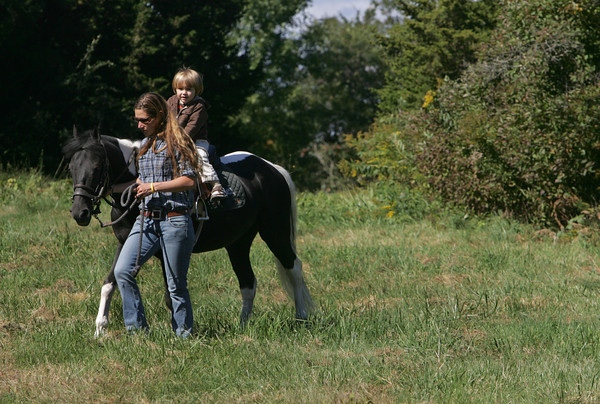 Essex: Cole CoteŽ, 3, of Manchester, takes a pony riide with Margo Kusulas from Turning Leaf Farm in Essex during the Fall Festival at the Cox Reservation Saturday afternoon.  The festival also offered offered pumpkin decorating, cider press demonstrations, hay rides, face painting and more. Mary Muckenhoupt/Gloucester Daily Times
