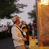 Gloucester: Brian Bicknell takes a drink of water while his son, William, 6 month, just hangs out as the two enjoy the evening at the Block Party on Main Street Saturday. Mary Muckenhoupt/Gloucester Daily times