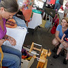 Gloucester: Kim Woods and her son Aidan, 2, of Gloucester watch Elizabeth Gramma spin yarn at the Gloucester Maritime Heritage Day at the Gloucester Maritime Heritage Center Saturday afternoon. Mary Muckenhoupt/Gloucester Daily Times