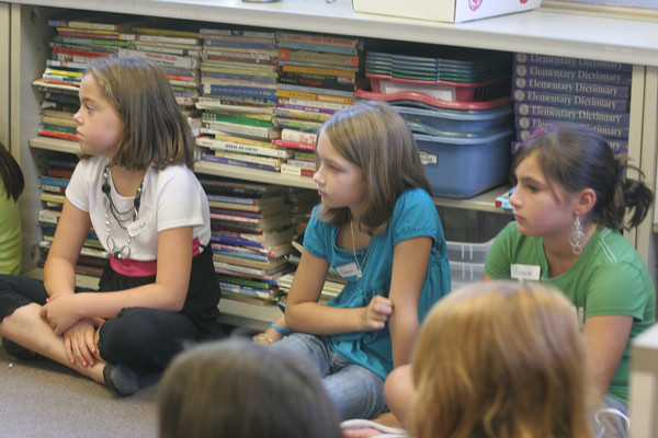 From left to right: 4th graders, Jordan Fears, Emma Twombly and Grace Sweetser listen to their teacher Ms. Clifton, as she reads the story of Crysanthemum yesterday on the first day of school at Rockport Elementary. Photo by Maria Uminski/ Gloucester Daily Times