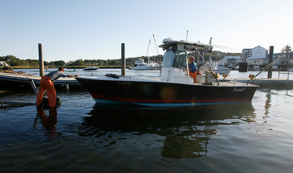Gloucester: Peter Smyrnios, left, helps guide Rick Pramas onto their boat trailer after a day of fishing. The two said they did not have much luck, but it was a still a beautiful day. Photo by Kate Glass/Gloucester Daily Times Tuesday, September 21, 2009