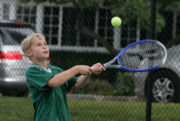 Manchester: Charlie Baker, 11, of Manchester keeps his eye ont he ball while working on his backhand during a friendly tennis match with his dad at Brook Street playground Wednesday afternoon. Mary Muckenhoupt/Gloucester Daily Times