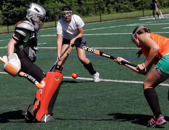 Manchester: Hornets goalie Vicki Grimes blocks a shot by Katie Gavin as Madeline Huleatt looks on during practice. Photo by Kate Glass/Gloucester Daily Times Wednesday, September 2, 2009