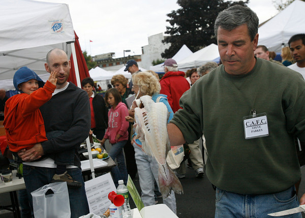 Gloucester: Gavin Doyle, 4, of Gloucester cheers in the arms of his father, Bill Doyle, while watching Steve Parkes fillet a fish at the Cape Ann Farmers Market. Gavin was very interested in the demonstration and watched it several times. Photo by Kate Glass/Gloucester Daily Times Thursday, September 17, 2009